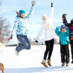 family happily jumping in the snow